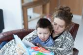 Little boy and his mother reading a story book together at home — Stock Photo