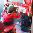 Постер, плакат: Rear view of a boy playing driving game at video game arcade