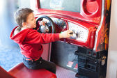 Side view of a little boy playing driving game at video game arcade — Stock Photo
