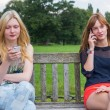 Two girls on bench in park calling mobile — Stock Photo #76014783
