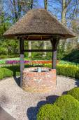 New waterwell with bucket in park — Stock Photo