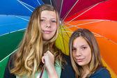 Two teenage girls under colorful umbrella — Stock Photo
