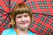 Young blonde girl under umbrella in rain — Stock Photo