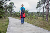 Woman hiking on wooden path in nature — Stock Photo