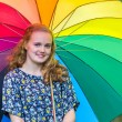 Teenage girl under umbrella with various colors — Stock Photo #76058009