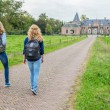 Two girls walking on road leading to castle — Stock Photo #76058093