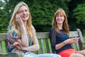 Two girls sitting on bench in park with mobile — Stock Photo