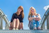 Two girls sitting on metal bridge with blue sky — Stock Photo