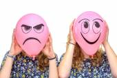 Two girls holding pink balloons with facial expressions — Stock Photo