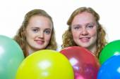 Two girls behind various colored balloons — Stock Photo