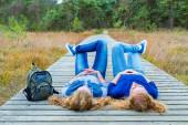 Two girls lying on their backs on path in nature — Stock Photo