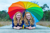 Two girls lying in nature under colorful umbrella — Stock Photo