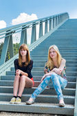 Two dutch girls sitting on metal bridge — Stock Photo
