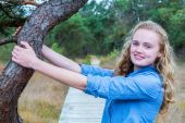 Blonde dutch girl holding tree trunk in nature — Stock Photo