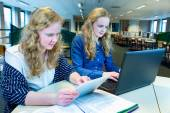 Two dutch girls working on computer and tablet in computer class — Stock Photo