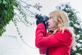 Young dutch woman photographing snow on branches — Stock Photo