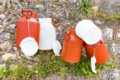 Hanging plastic white and brown milk cans — Stock Photo