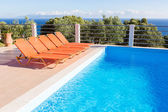 Row of orange loungers near blue swimming pool — Stock Photo