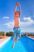 Dutch teenage boy jumping high above blue swimming pool — Stock Photo