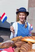 European woman with breads waving with dutch flag — Stock Photo