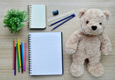 Blank paper, color paint and bear doll on the wood table - Top view — Stock Photo