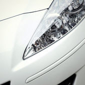 Detail on the headlight of a white car — Stock Photo