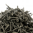 A lot of black drywall screws on a white background — Stock Photo #60675579