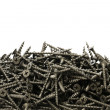 A lot of black drywall screws on a white background — Stock Photo #60675899
