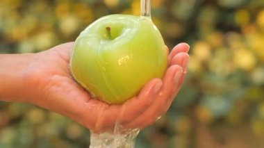 Green apple in hand under flowing water slow motion — Stock Video