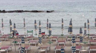 Geschlossene sonnenschirme, strand bei sonnenuntergang — Stockvideo
