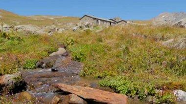 Paisaje alpino con una casa de piedra — Vídeo de stock