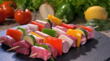 Raw meat skewers on stone plate rotating — Stock Video