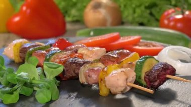 Grilled meat skewers on stone plate rotating — Stock Video