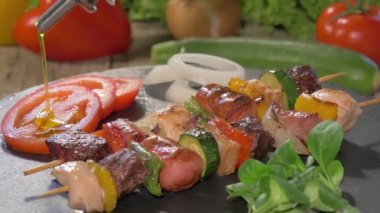 Pouring olive oil over grilled meat skewers — Stock Video