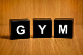 GYM or gymnasium or gymnastic services word on black block — Stock Photo
