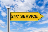 Yellow road sign with 24 hours a day, 7 days a week service word — Stock Photo