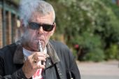 Man in sunglasses puffing on an e-cigarette — Stock Photo