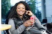 Vivacious African woman listening to music — Stock Photo
