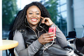 Vivacious African woman listening to music — Stockfoto