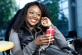 African woman listening to music outdoors — Stockfoto
