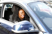 African woman smiling as she drives her car — Stock Photo