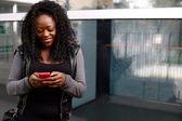 Young African woman sending an sms on her mobile — Stock Photo