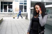 African woman talking on her mobile in the street — Stock Photo