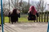 Rear View of Two Teenage Girls Swinging on Swings — Stock Photo