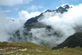 Meadow stones and mountain between clouds nearby Sustenpass — Stock Photo