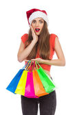 Surprsed christmas girl with shopping bags — Stock Photo
