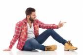 Relaxed man in lumberjack shirt pointing — Photo