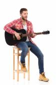 The guitarist on a chair — Stock Photo