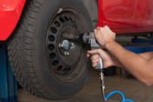 Changing the wheel with an impact wrench — Stockfoto