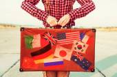 Woman holds suitcase with stamps flags — Stock Photo